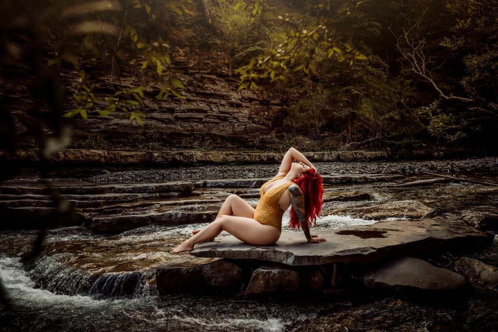 calgary boudoir photography redhead poses in the river waterfall yellow lingerie red hair sexy pictures