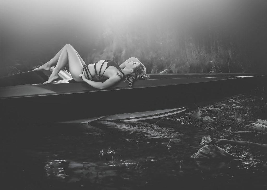 boudoir photography on a boat in a lake with swimsuit lingerie at sunset monochrome