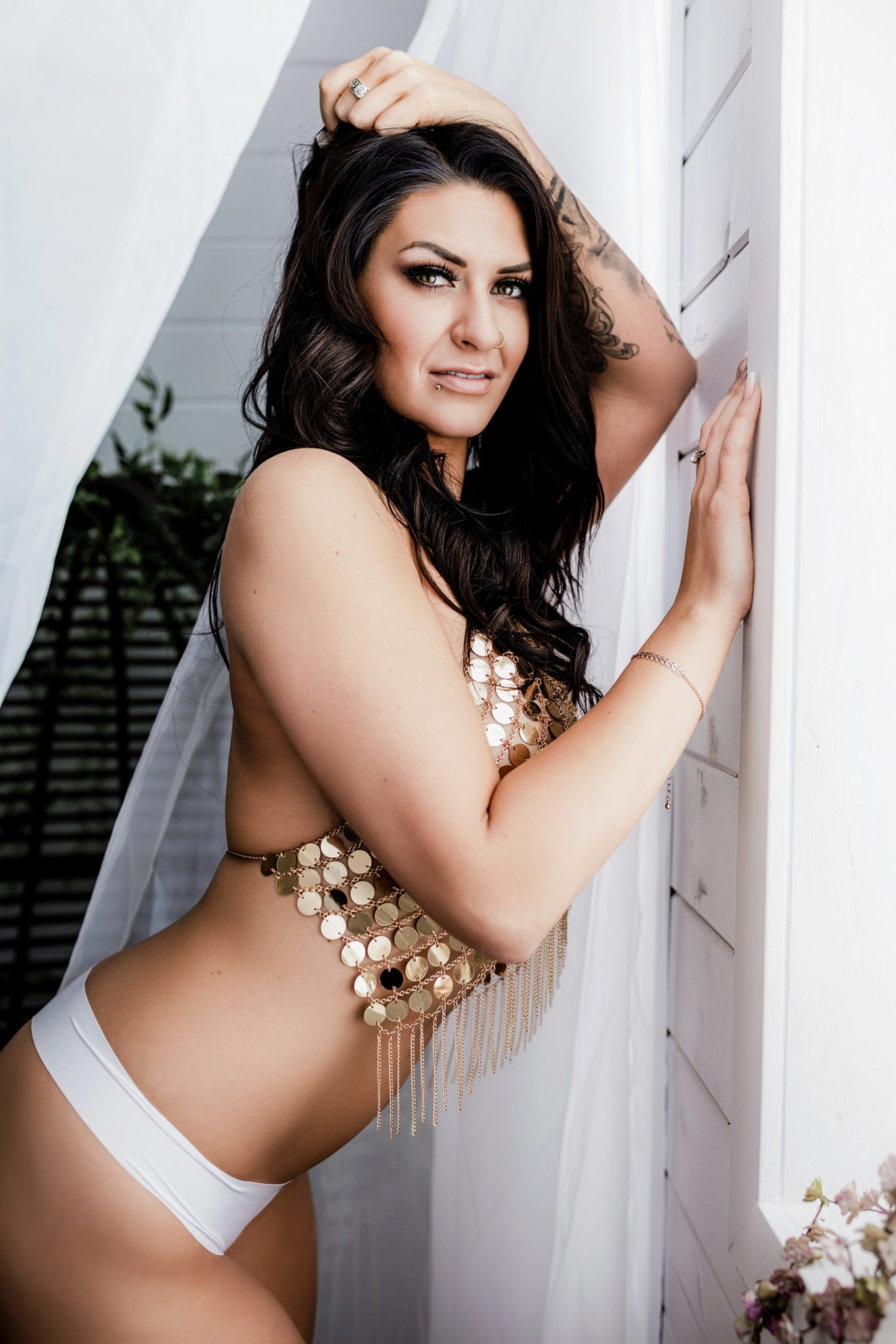 Boudoir photography inside the studio wearing a golden body chain and white underwear